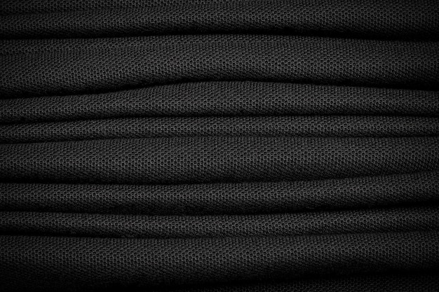 Many of black shirt background. dark textile material.