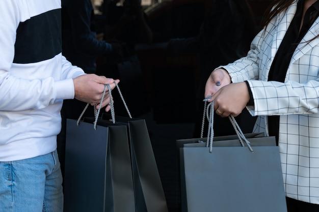 남성과 여성의 손에 많은 검은색 쇼핑백이 있습니다. 쇼핑 후. 손에 구매. 검은 금요일 개념입니다.