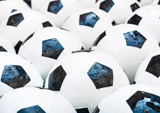 Many black and white soccer balls. football balls in a water