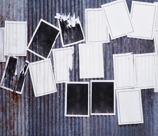Много пустых старых рекламных плакатов на ржавой гофрированной металлической цинковой стене