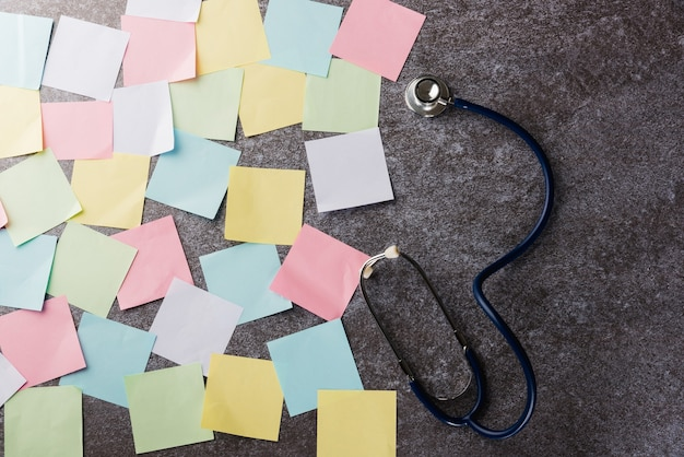 Above many blank paper stick note list with doctor stethoscope on concrete board