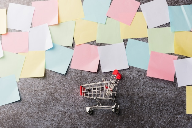 Above many blank paper stick note list with the shopping cart on concrete board