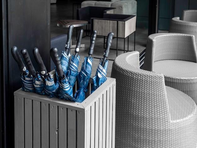 Многие синие сложенные зонтики в контейнерной стойке для зонтов, хранящейся в ящике, подготавливают гостей к выходу на улицу в дождливый день или в солнечную погоду в отеле.
