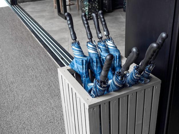 傘立てコンテナボックス収納サービスの青い折り畳まれた傘の多くは、雨の日やホテルの晴れた日に屋外にゲストを準備します。