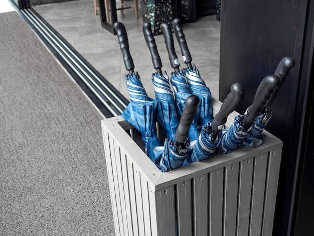 Many blue folded umbrellas in umbrella stand container box stored service prepare for guest to outdoor in raining day or sunny in the hotel.