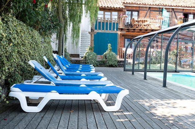 Many blue lounge chairs beside the pool