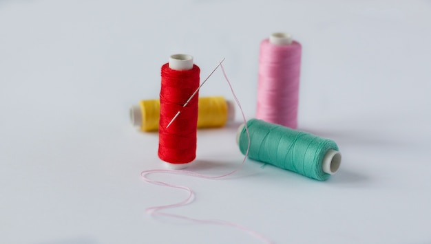 Many bobbins of bright sewing thread with a needle