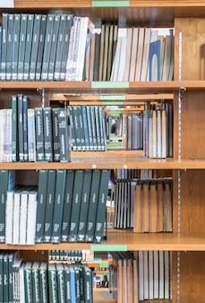 도서관의 나무 선반에 쌓인 많은 책 정렬