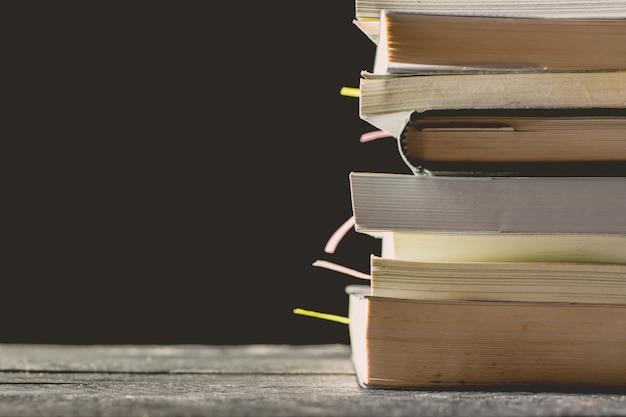 많은 책은 밝은 빛을 가진 어두운 방에 나무 테이블에 쌓여 있습니다.