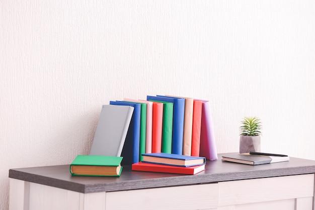 가벼운 벽 근처 테이블에 많은 책