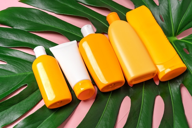 日焼け止めスキンケア製品とピンクのモンステラの葉が入った多くのボトル。