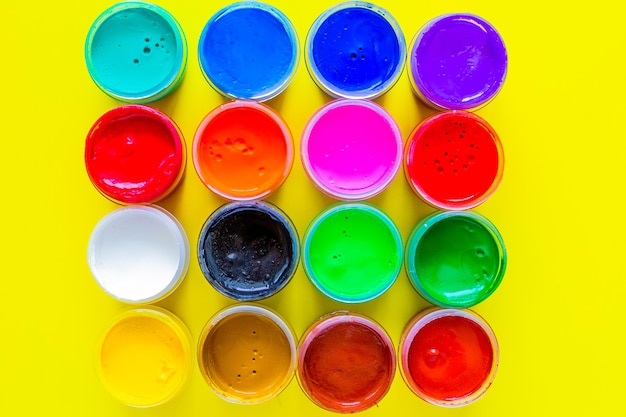Many bright cans of paint stand together on a yellow background closeup top view flat lay copy space...