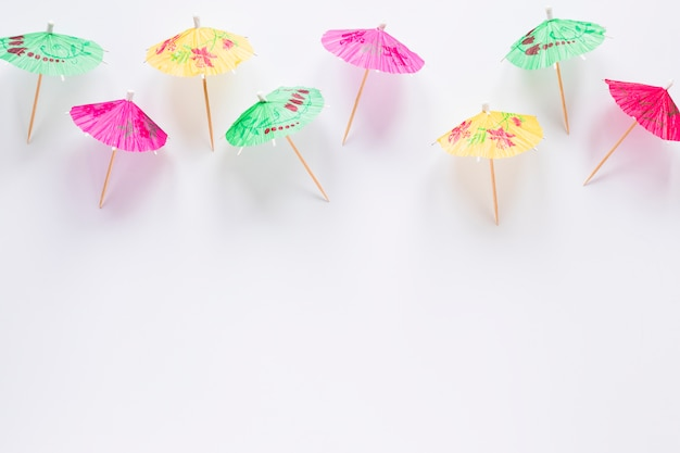 Many bright cocktail umbrellas on table