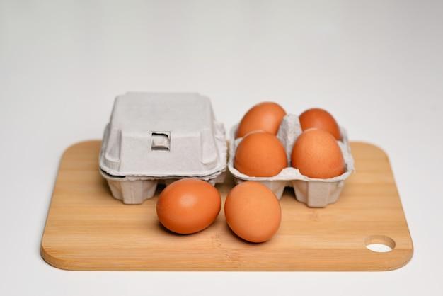 Многие коричневые яйца, изолированные на белых куриных яйцах, свежие в картонной упаковке.