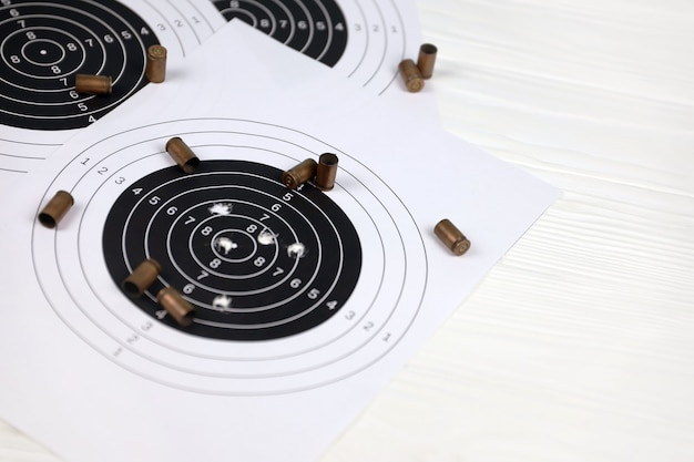 Many bullets with shooting targets on white table in shooting range polygon. training for aiming and shooting accuracy