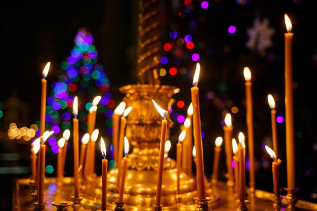 Many burning candles stand in a golden stand in the church. selective focus
