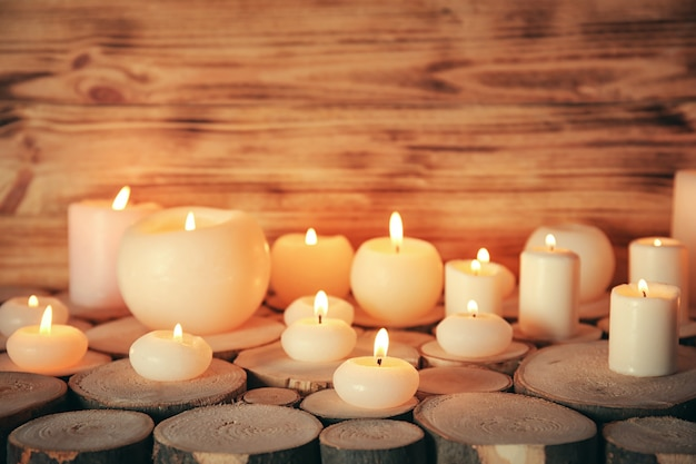 Many burning candles on wooden surface