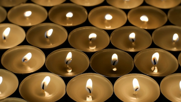 Many burning round small candles with reflections are burning in dark.