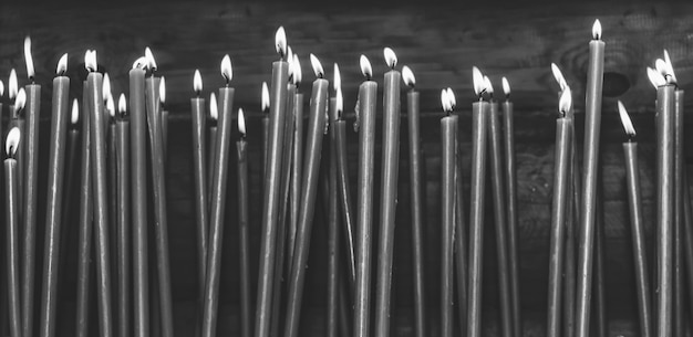 Many burning wax candles in the temple, black and white photo