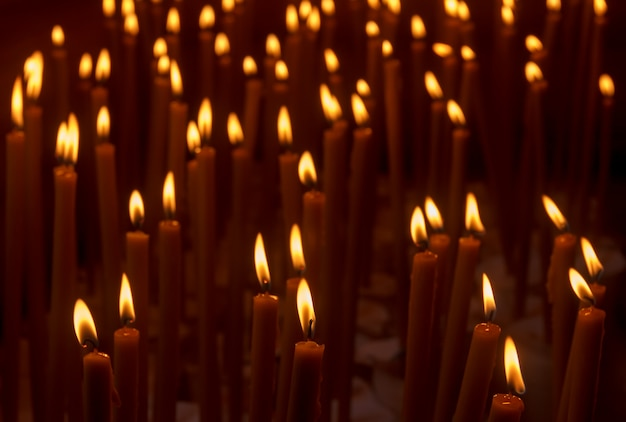 Many burning wax candles in the temple
