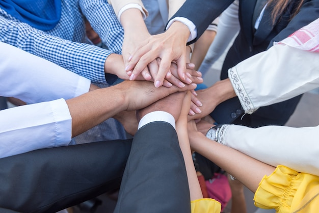 Many business people join hands together for the first agreement to do business together.