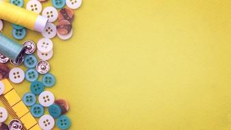 Many button and colored thread for sewing on yellow cloth background.