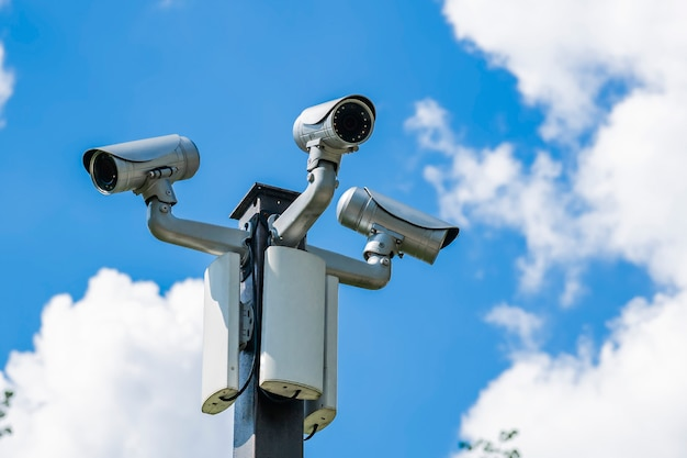 Many cameras video surveillance on a pole against the sky
