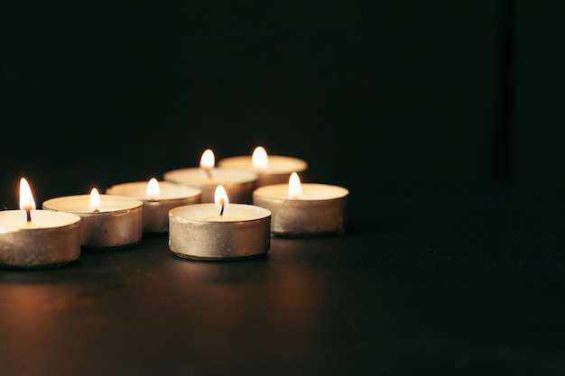 Many candles burning at night. many candle flames glowing on dark background