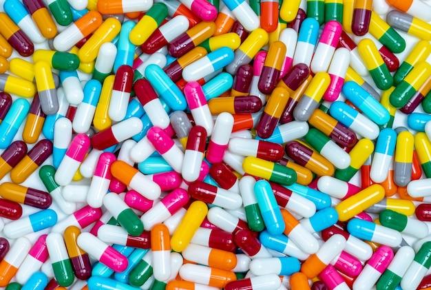 Множество таблеток в капсулах. таблетки капсулы вид сверху. полнокадровые разноцветные капсульные таблетки.