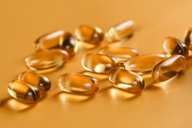 Многие капсулы омега-3 на желтом фоне. закройте вверх. концепция здравоохранения.