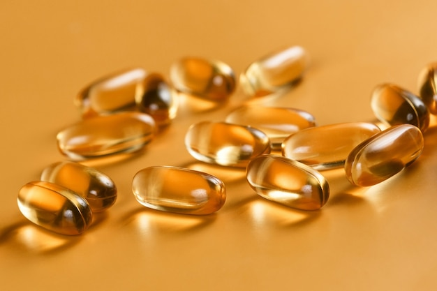 Many capsules omega 3 on yellow background. close up. health care concept.