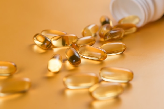 Many capsules omega 3 on yellow surface