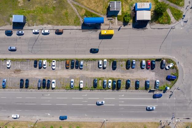 도시 외곽에있는 2 개의 도로 사이에 자발적으로 가로채는 주차장에 많은 자동차가 주차되어 있습니다.