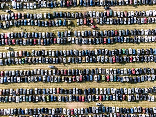 Многие машины припаркованы в поле. автомобильный фон. вид сверху