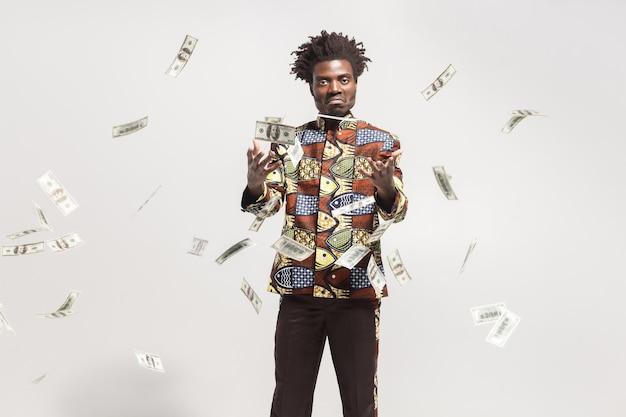 많은 현금이 국가 콩고 의상을 입은 아프리카 남자 근처에서 날아갑니다.