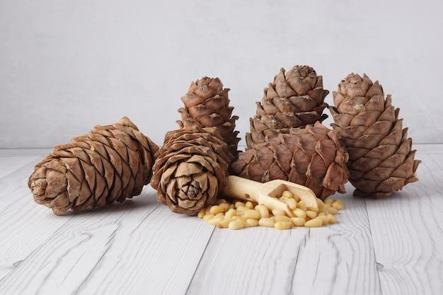 Многие кедровые шишки и орехи на деревянной лопатке