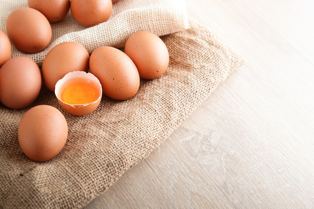 Many chicken eggs are placed on a brown cloth