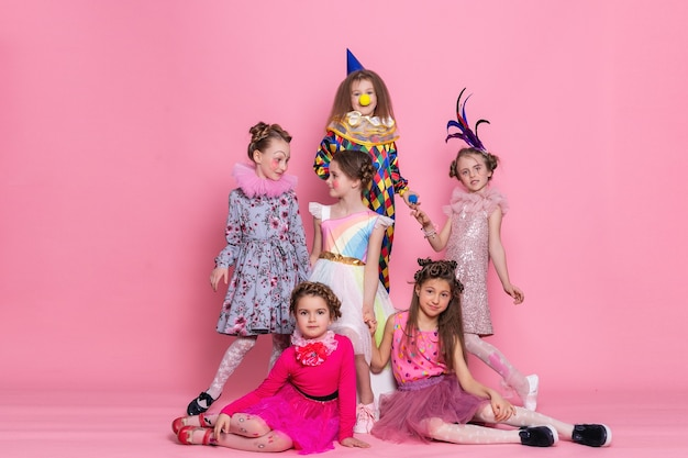 Many children in costumes on a pink background. happy birthday. celebrating. many kids in halloween costumes