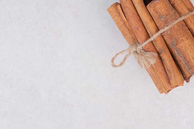 Many of cinnamon sticks on white table