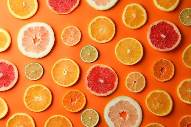 Многие цитрусовые ломтики на оранжевом фоне, вид сверху