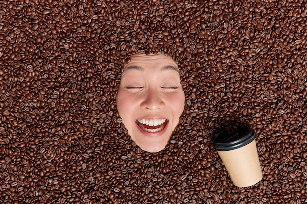 Many coffee beans around drinks espresso from paper disposable cup keeps eyes closed smiles broadly enjoys pleasant aroma or scent