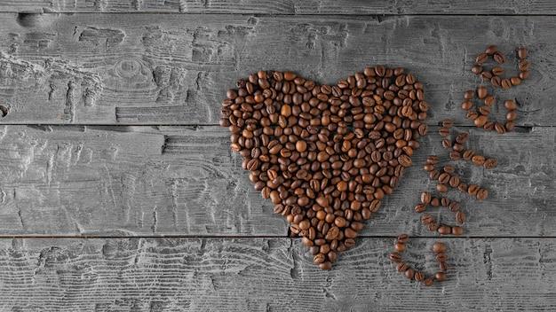 多くのコーヒー豆は黒いテーブルにハートの形に折りたたまれています。上からの眺め。人気の飲み物の準備のための穀物。