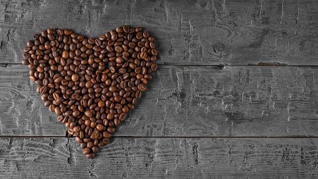 多くのコーヒー豆は黒い木製のテーブルにハートの形に折りたたまれています。上からの眺め。人気の飲み物の準備のための穀物。