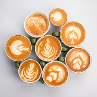 Many coffee latte cup on white table, top view