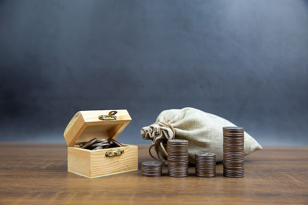 Many coins are stacked in a graph shape and many coins in a wooden crate for money saving ideas financial planning and insurance.