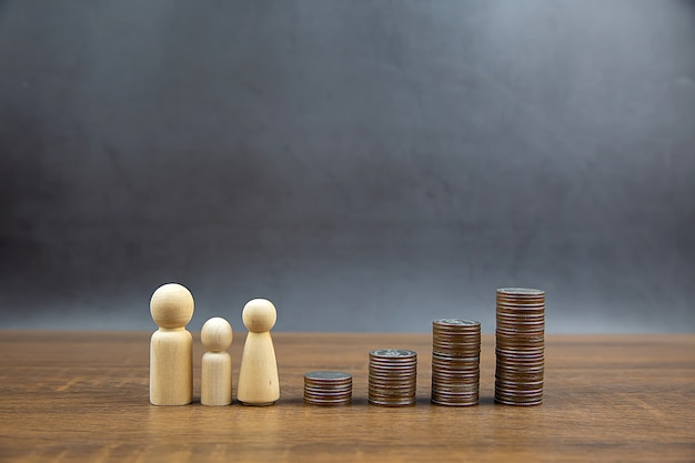 Many coins are stacked in a graph shape with family icons for money saving ideas and financial planning insurance.