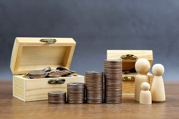 Many coins are stacked in a graph shape with family wooden doll for money saving ideas.