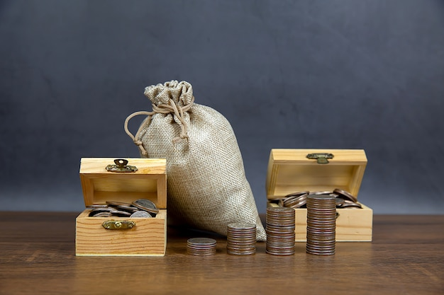 많은 동전은 그래프 모양으로 쌓여 있고 돈 절약을 위해 나무 상자에 많은 동전이 있습니다.