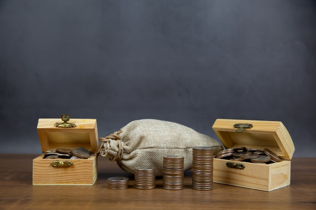 Многие монеты сложены в форме графа и много монет в деревянном ящике.
