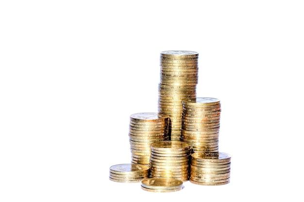 Многие монеты в столбце, изолированном на белой стене.